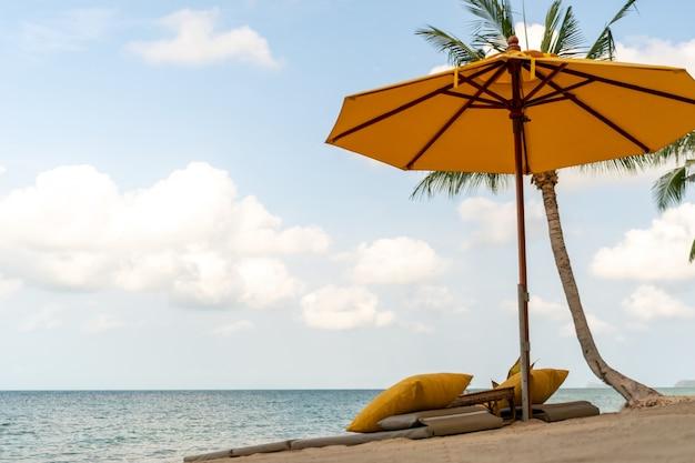 Parasol i krzesło na tle tropikalnej plaży latem z niebieskim niebem