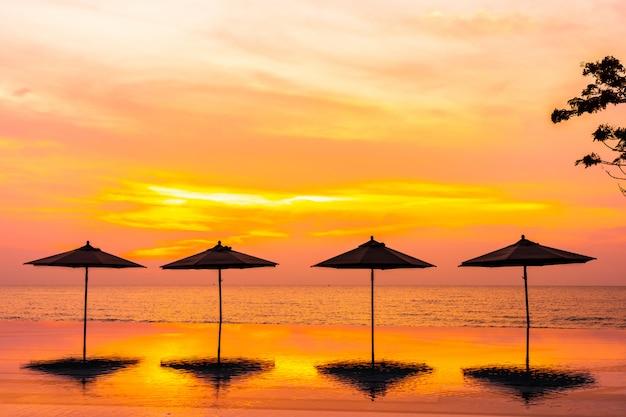 Parasol i krzesło wokół basenu blisko plaży oceanu morskiego o wschodzie lub zachodzie słońca