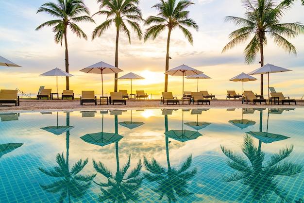 Parasol i krzesło wokół basenu w hotelowym kurorcie z wschodem słońca rano - koncepcja wakacji i wakacji