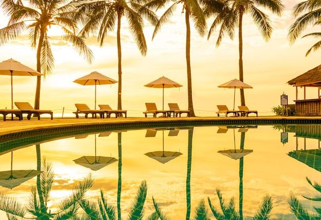 Parasol i krzesło wokół basenu w hotelu wypoczynkowym na podróże rekreacyjne i wakacje w pobliżu plaży nad morzem o zachodzie słońca lub wschodzie słońca