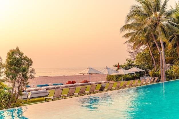 Parasol i krzesło wokół basenu z widokiem na morze na wakacje wakacje koncepcja podróży