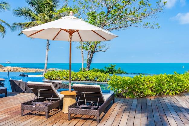 Parasol i krzesło wokół odkrytego basenu w hotelowym kurorcie z widokiem na morze na wakacje w podróży