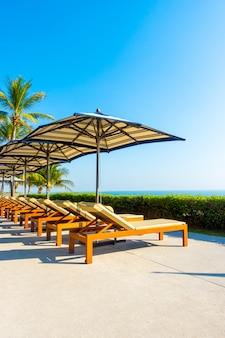 Parasol i krzesło wokół odkrytego basenu w hotelu i ośrodku