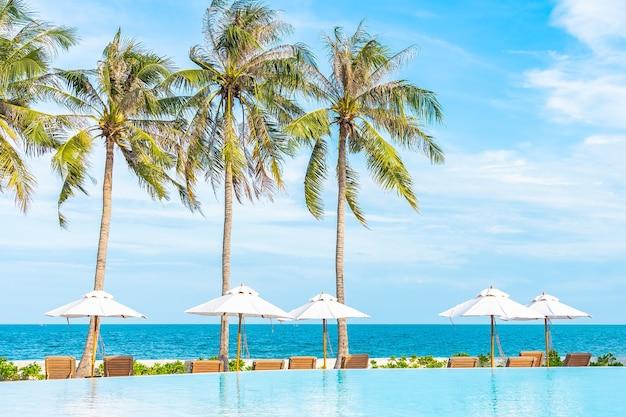 Parasol i leżak wokół odkrytego basenu w hotelowym kurorcie z plażą morską i palmą kokosową