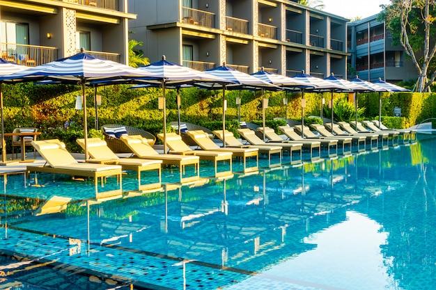 Parasol i łóżko basenowe wokół odkrytego basenu w hotelowym kurorcie na wakacje