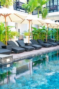 Parasol i łóżko leżak wokół basenu - koncepcja wakacji i podróży wakacyjnych