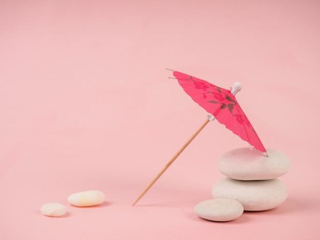 Parasol koktajlowy. różowy papierowy koktajlu parasol odizolowywający na menchiach. papierowy różowy parasol na różowych kamieniach, w pobliżu białych kamieni, koncepcja wypoczynku i minimalizmu
