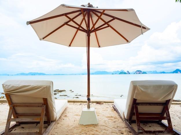 Parasol plażowy i dwa puste drewniane leżaki z poduszkami z tkaniny na piaszczystej plaży z wyspą, morzem, chmurą i błękitnym niebem. para leżak na świeżym powietrzu z widokiem na morze.