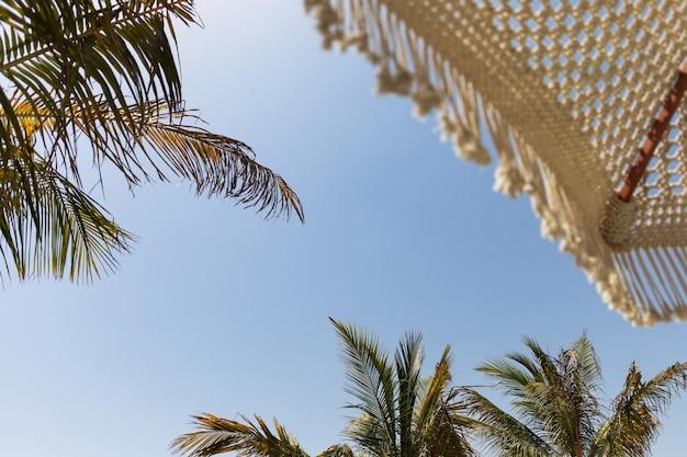 Parasol plażowy i palmy na tle błękitnego nieba przy słonecznej pogodzie.