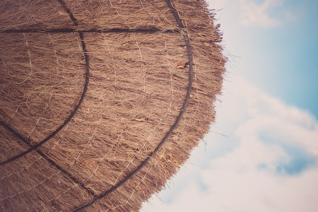 Parasol plażowy suszonych liści w pobliżu morza. koncepcja wakacji podróży.