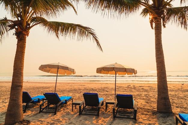 Parasol plażowy z palmą i plażą morską o wschodzie słońca - koncepcja wakacji i wakacji