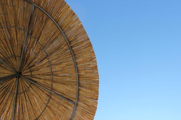 Parasol z bambusa. skopiuj miejsce. widok z góry na plażę ze słomy.