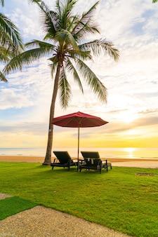 Parasol z krzesłem z plażą morską i wschodem słońca w godzinach porannych - koncepcja wakacji i wakacji