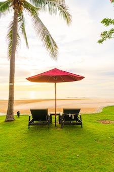 Parasol z krzesłem z plażą morską i wschodem słońca w godzinach porannych