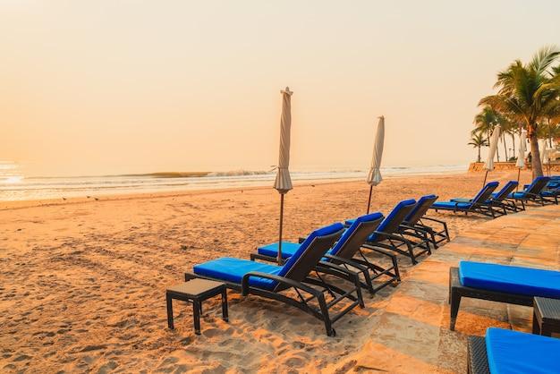 Parasole i leżaki na plaży z palmami o wschodzie słońca