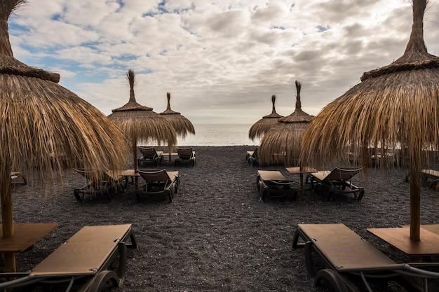 Parasole i siedzenia na plaży na wyspie teneryfa. miejsce na wakacje bez nikogo. czas zamknięty z powodu złej pogody
