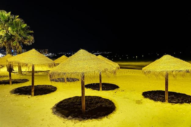 Parasole na plaży w nocy oświetlone reflektorami.