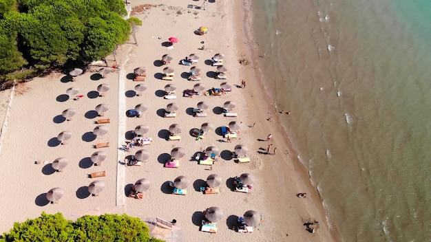Parasole plażowe na piasku obmywanym spokojną, czystą wodą turkusowego morza śródziemnomorskiego.