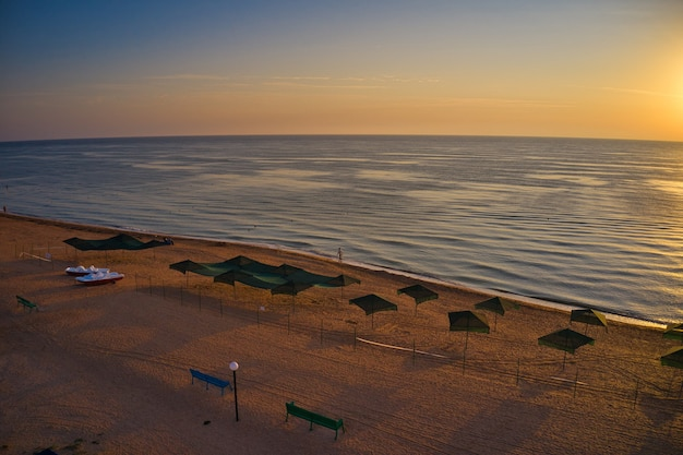 Parasole plażowe o wschodzie słońca. prąd morski płynie na tle fal na pięknym morzu