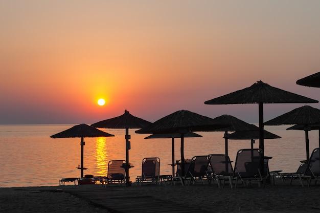 Parasole plażowe o zachodzie słońca, leżaki, gorący zachód słońca na plaży
