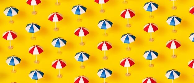 Parasole plażowe wzór na żółtym tle, koncepcja wakacji letnich, obraz panoramiczny