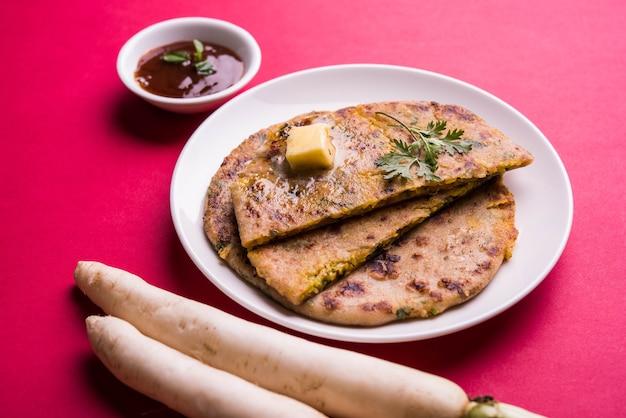 Paratha nadziewana daikon, rzodkiew lub mooli, podana na talerzu z masłem i keczupem pomidorowym, na kolorowym lub drewnianym tle. selektywne skupienie