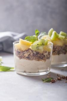 Parfait domowej roboty jogurt z muesli, owoców kiwi, ananasa i orzechów w szklance na zdrowe śniadanie na betonowym tle