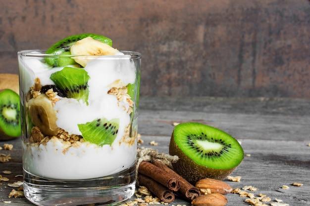 Parfait domowej roboty jogurtowy z muesli, kiwi, bananem, cynamonem i orzechami