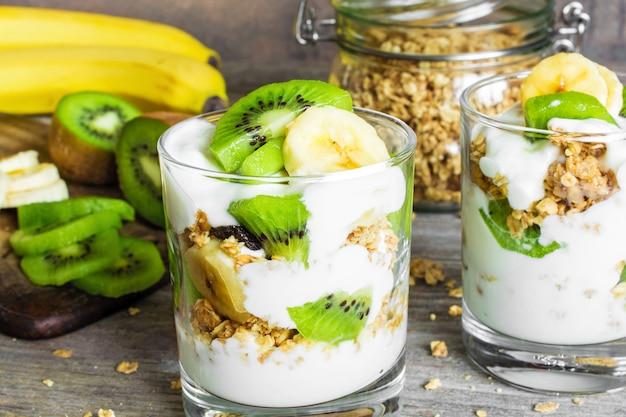 Parfait domowej roboty jogurtowy z muesli, kiwi, bananem i orzechami
