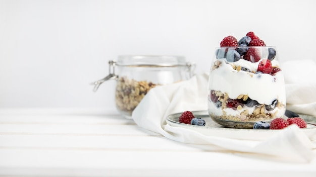 Parfait granola z jagodami i jogurtem z miejscem na kopię na białym tle