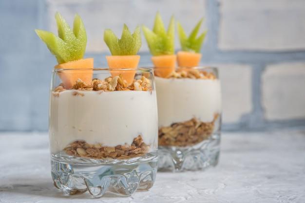 Parfait ze świeżych owoców z jogurtem i muesli na śniadanie wielkanocne