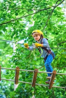 Park linowy - centrum wspinaczkowe. beztroskie dzieciństwo. małe dziecko wspinaczka w parku rozrywki