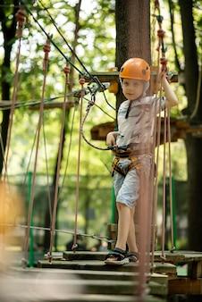 Park linowy dla dzieci. młody chłopak w klapie wspina się na przeszkody. aktywny wypoczynek sportowy dziecka.