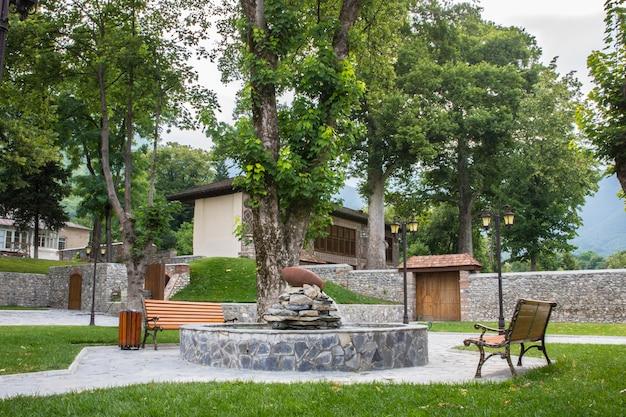 Park miejski z ławkami i kominkiem.