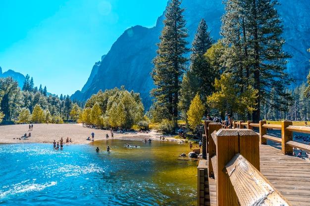 Park narodowy yosemite, kalifornia stany zjednoczone. młody mężczyzna rzucający się na łeb na szyję do wody przy moście swinging w dolinie yosemite
