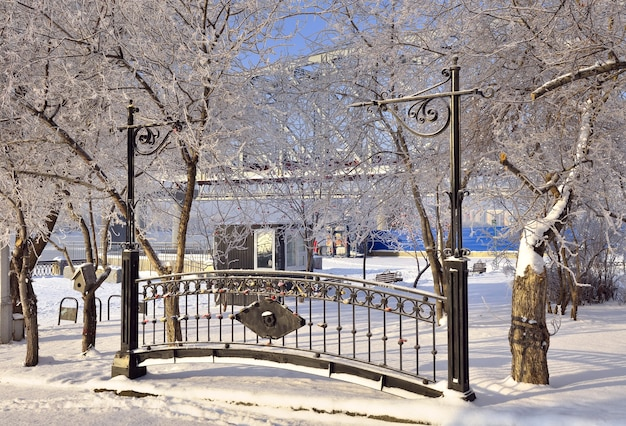 Park początek miasta zimą ogrodzenie pamięci wśród śniegu na nasypie nowosybirskim
