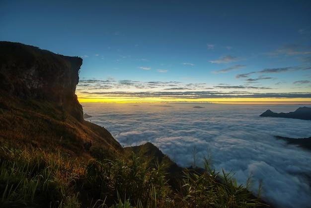 Park przyrody phu chi fa o świcie z nieba o zmierzchu w chiang rai, północnej prowincji tajlandii. słynny cel podróży, aby zobaczyć poranny wschód słońca i morze mgły na szczycie górskiego szczytu w zimie.