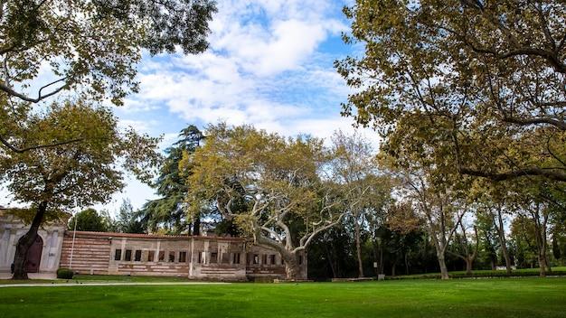 Park w stambule z wieloma drzewami, zielonymi trawnikami i starą konstrukcją, turcja