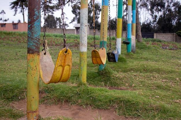 Park z dużą ilością starych, zwietrzałych huśtawek łańcuchowych