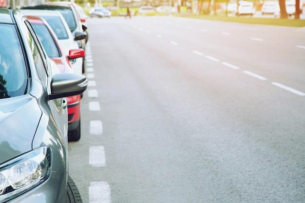 Parking samochodowy na zewnątrz, samochody w rzędzie parking na poboczu drogi.