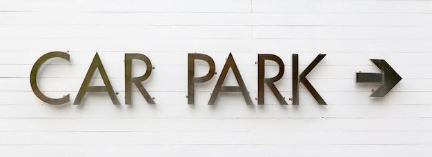 Parking samochodowy znak z strzała na białej drewnianej desce.