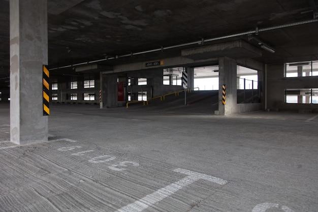 Parking wielopoziomowy z jasnymi oznakowaniami w ciągu dnia z pustymi miejscami parkingowymi, kolumnami i płytkami chodnikowymi
