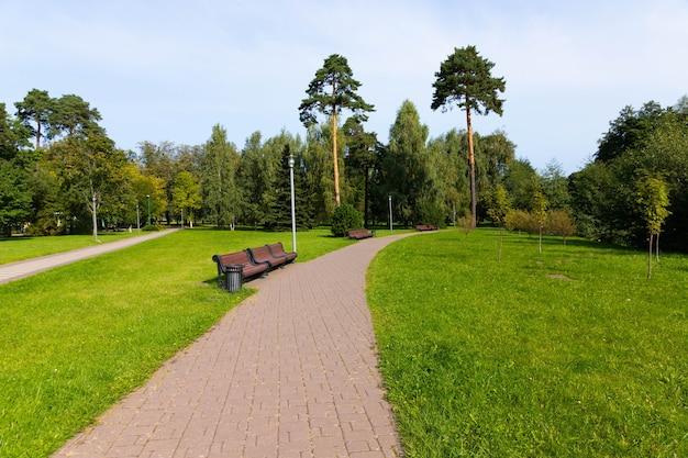 Parkowa ścieżka z ławkami, zieloną trawą i drzewami.