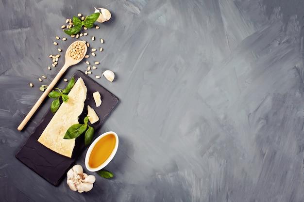 Parmezan, oliwa z oliwek, bazylia, czosnek, orzeszki piniowe - świeże składniki do przepisu na pesto. włoska koncepcja kuchni