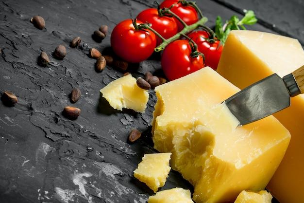 Parmezan z pomidorami, orzeszkami pinii i listkami mięty na czarnym rustykalnym stole.