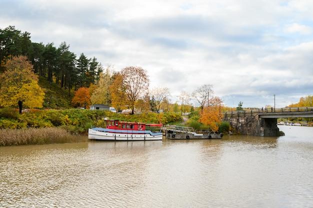 Parowiec, longboat na molo. jesienny krajobraz.