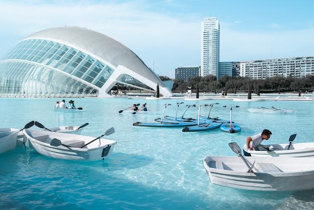 Partia łodzi na wodzie z ludźmi w pobliżu budynku w ciągu dnia
