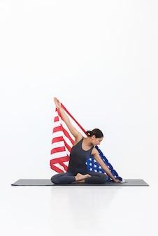 Partiot kobieta z amerykańską flagą robi siedzącej jogi na macie na białym tle.