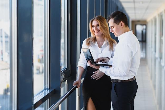 Partner biznesowy biura wyświetla statystyki danych informacyjnych online. szef i sekretarz lub asystent pracują jako zespół. zapytaj kolegę o opinię. biznesmen trzymać laptopa surfowanie po internecie z kolegą.