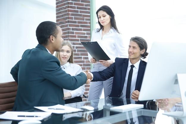 Partner biznesowy uścisk dłoni na spotkaniu w nowoczesnym biurowcu